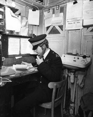 PC 64B, Alan Saunders, using the 'modern' telephone that replaced the original fitted instrument, which was situated in the corner to the left of the picture, where a dark wooden box protrudes. Scanned by Alan M. 20/03/00 from print
