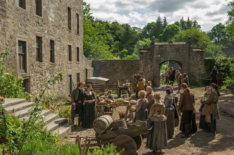Claire y Jamie en el patio de Lallybroch, el Midhope Castle en la vida real